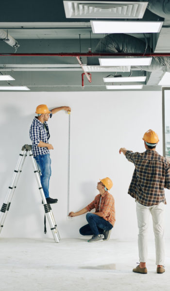 Vertical long shot of professional construction workers taking length measurements using tape rule, copy space